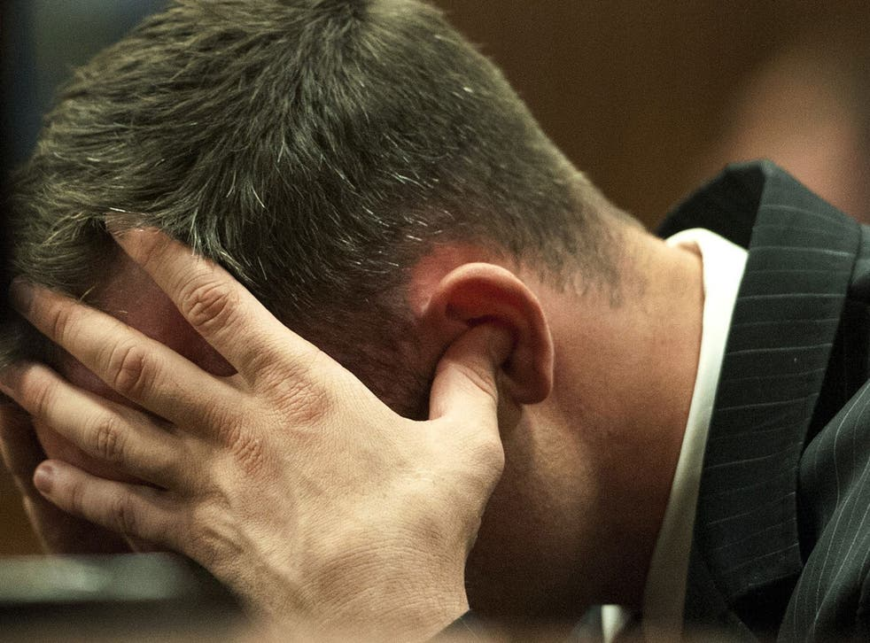 Oscar Pistorius holds his head in his hands in the dock during cross examination of a witnesses in court in Pretoria