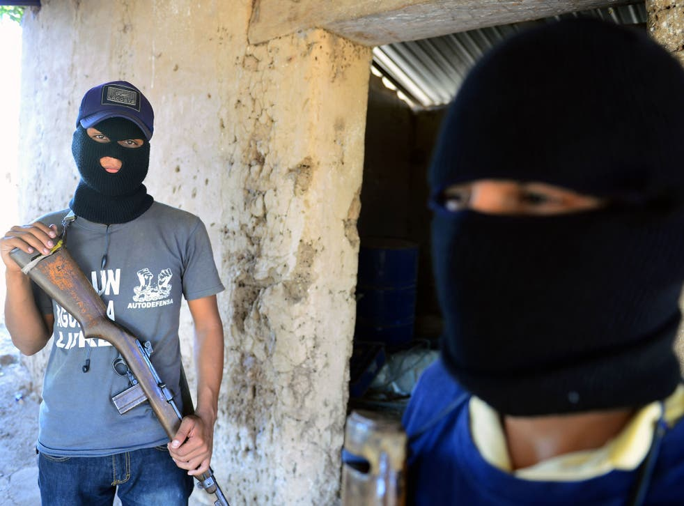 Two former informants of the Templar Knights drug cartel pose in Michoacan state, Mexico