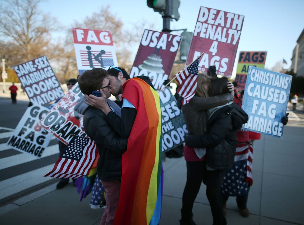 Two same sex couples kiss in front of Westboro Baptist Church protesters at the US Supreme Court. The high court was hearing arguments on whether Congress can withhold federal benefits from legally wed gay couples by defining marriage as only between a ma