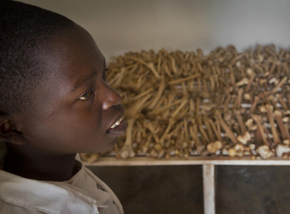 Nikeyimana Obadia, 12, who lives nearby, stands by rows of human bones that form a memorial to those who died in the redbrick church that was the scene of a massacre during the 1994 genocide, in the village of Nyarubuye, eastern Rwanda