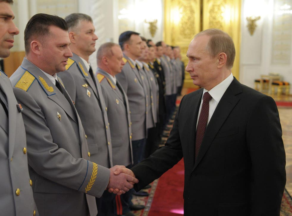 Vladimir Putin meets newly promoted officers yesterday from the Russian armed forces, which he praised for their role in Crimea