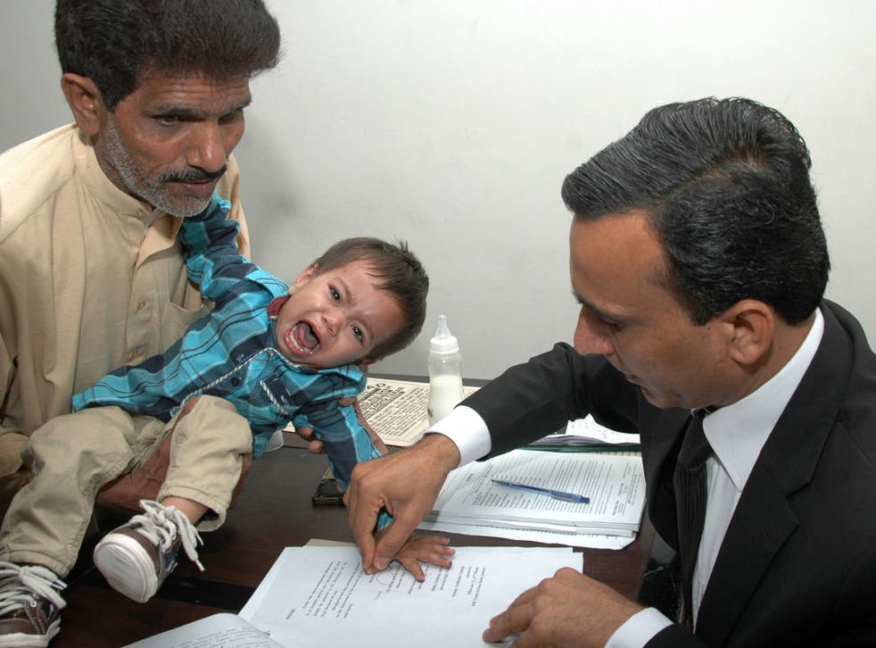 Nine-month-old Muhammad Mosa Khan has his finger prints taken by an official in court