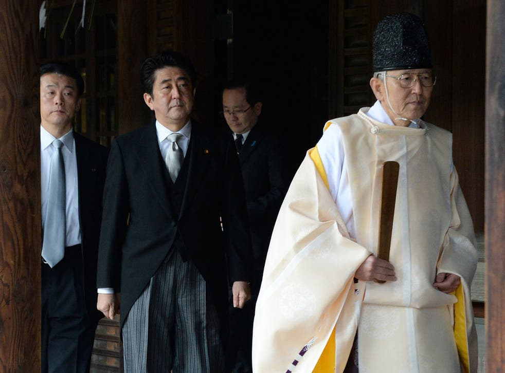 A Shinto priest (R) leads Japanese Prime Minister Shinzo Abe (C) as he visits the controversial Yasukuni war shrine in Tokyo on December 26, 2013, in a move Beijing condemned as 'absolutely unacceptable'. Abe described his visit, which is certain to roil