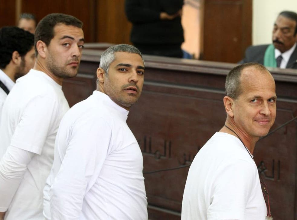 Australian journalist Peter Greste (R), Mohamed Fahmy, Baher Mohamed stand in front of the judge's bench during their trial for allegedly supporting a terrorist group and spreading false information, in Cairo, Egypt, 31 March 2014.