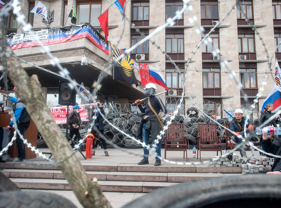 Masked pro-Russian activists guard barricades at the regional administration building in Donetsk