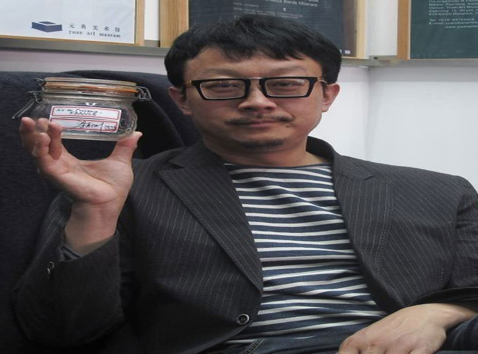 Beijing artist Liang Kegang poses with the jar of fresh air collected in Provence, France, in an art gallery in Beijing, China.
