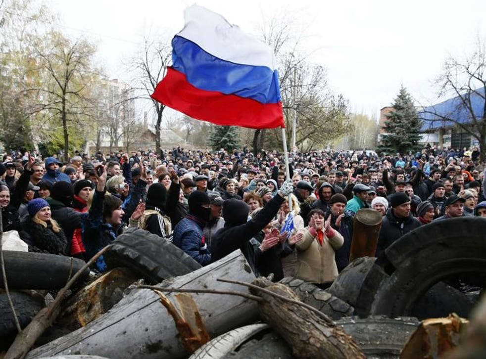 Pro-Russian protestors wave the Russian flag in front of the police headquarters in Slaviansk