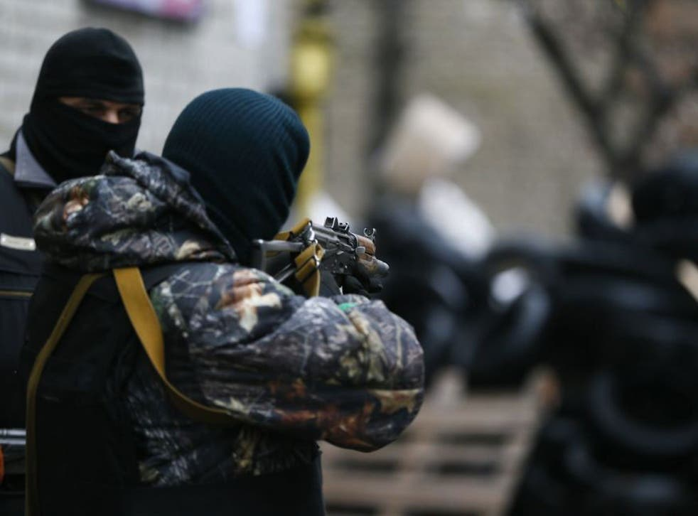 A pro-Russian armed man checks the gun sight of his weapon next to a barricade in front of the police headquarters in Slovyansk
