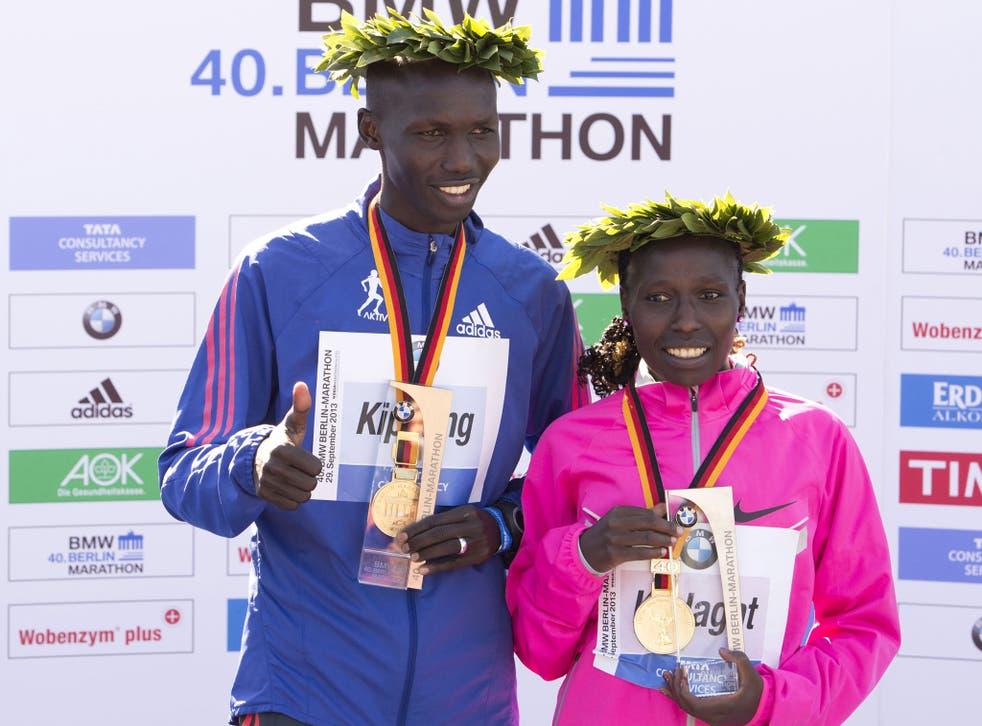 London Marathon winners Wilson Kipsang (left) and Florence Kiplagat (right), both from Kenya, pose on the podium