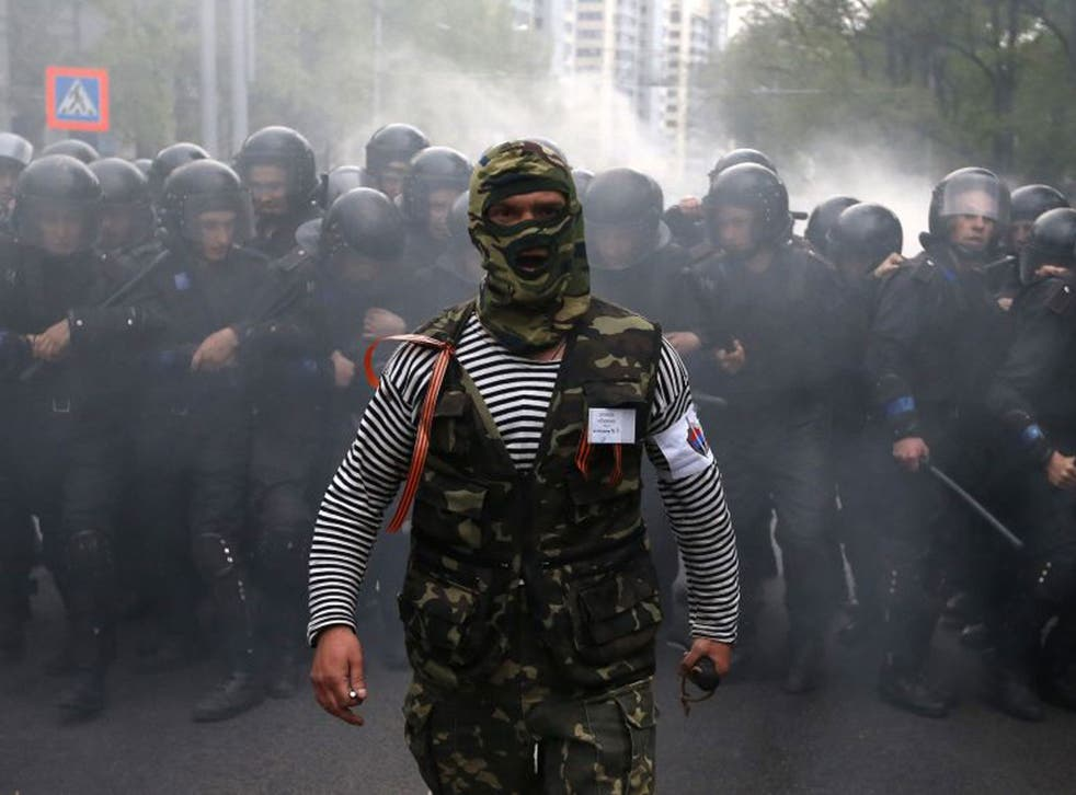A pro-Russian activist walks in front of Ukrainian riot police during a rally in Donetsk