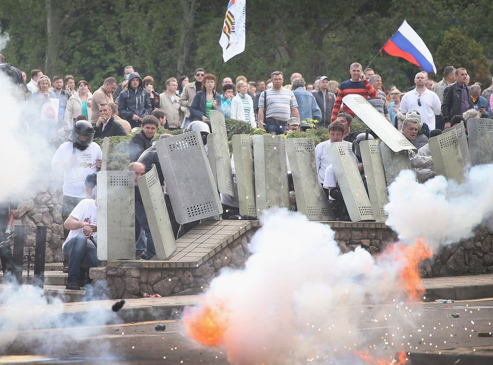 Police officers who retreated into the prosecutors office fire gas and stun grenades at pro-Russian activists who take cover behind shields taken from the police on May 1, 2014 in Donetsk, Ukraine. Activists marched to the prosecutor's office and overran