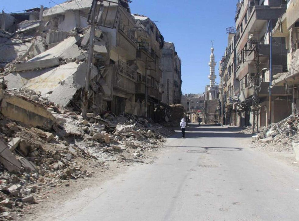 A resident walks alone down a ruined Damascus street