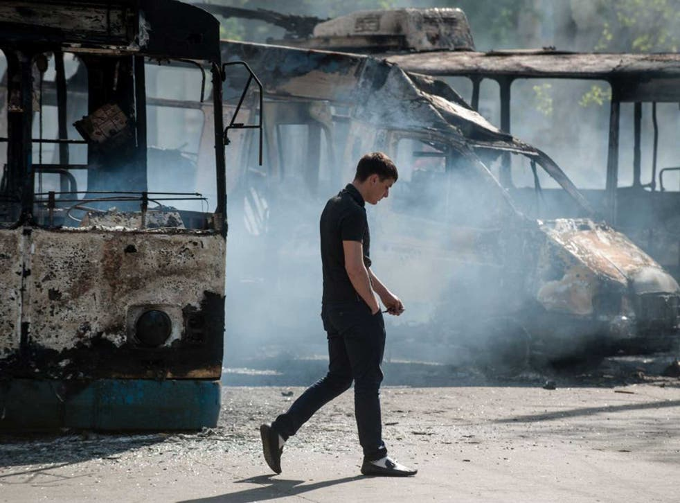 Metal and flesh: A man walks past a charred van and bus in Kramatorsk yesterday