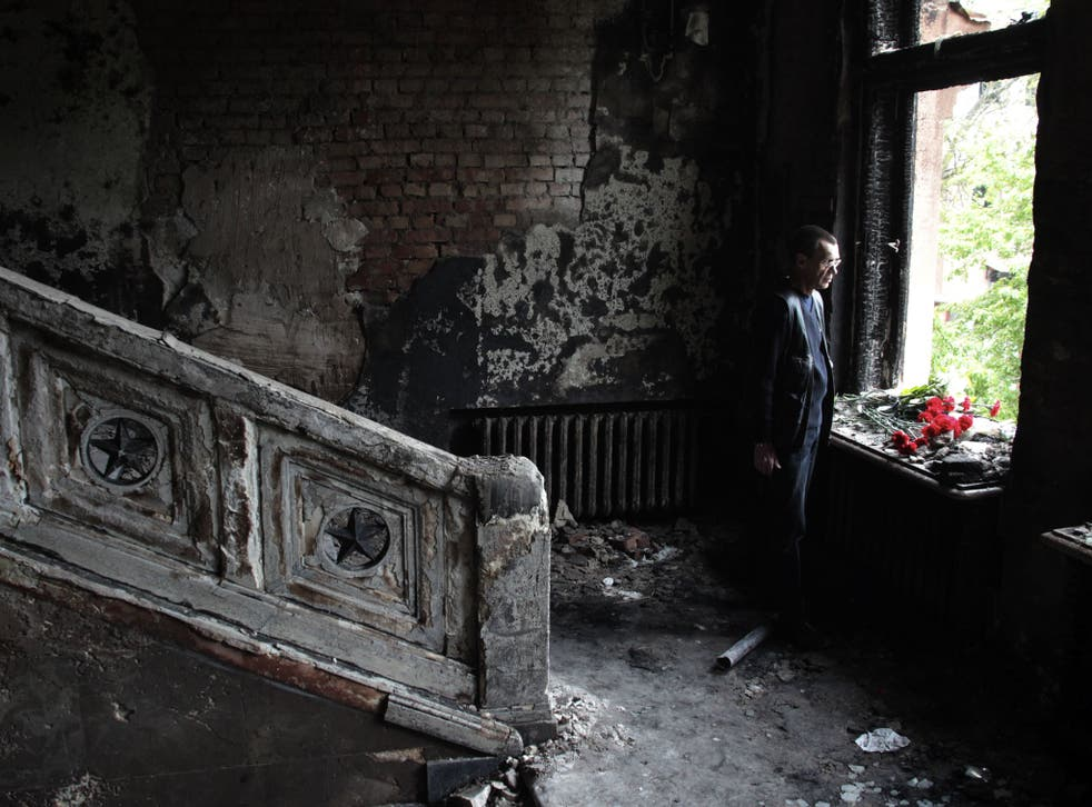 A man lays flowers inside the trade union offices in Odessa, where more than 40 people died – some from gunshot wounds, but most in a fire that tore through the building