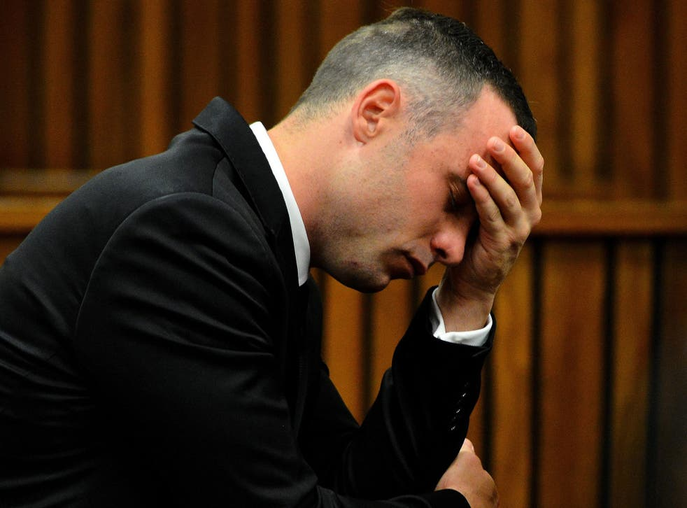 Oscar Pistorius holds his hand on his forehead in the dock at the high court in Pretoria