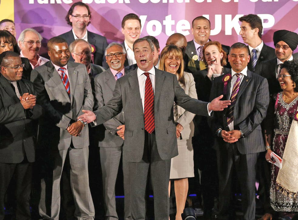Nigel Farage (centre) speaks on stage during a Ukip rally held at the Emmanuel Centre, London