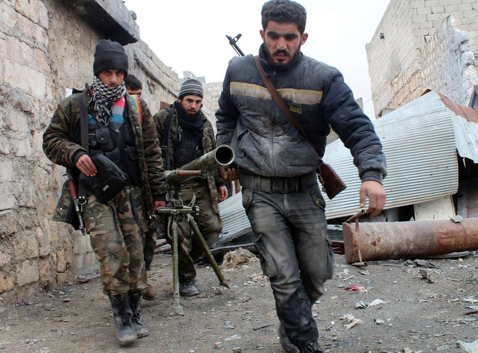 Opposition fighters carrying a rocket launcher during clashes against government forces in the Sheikh Lutfi area, west of the airport in the northern Syrian city of Aleppo