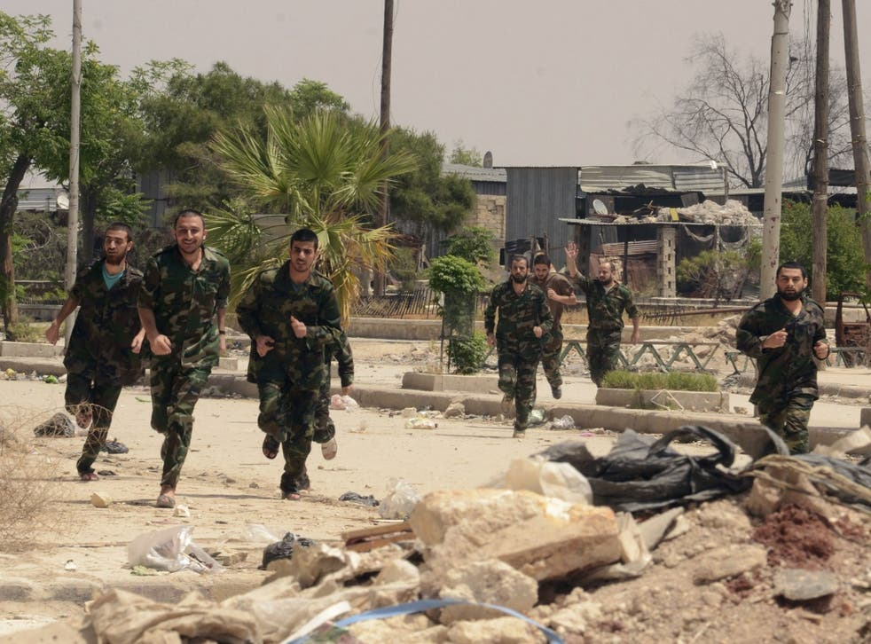 Forces loyal to Syria's President Bashar al-Assad run through Aleppo's Bustan al-Qasr crossing after their release by rebels. They were freed as part of a larger deal which saw the last remaining Syrian rebels in central Homs city evacuate their positions