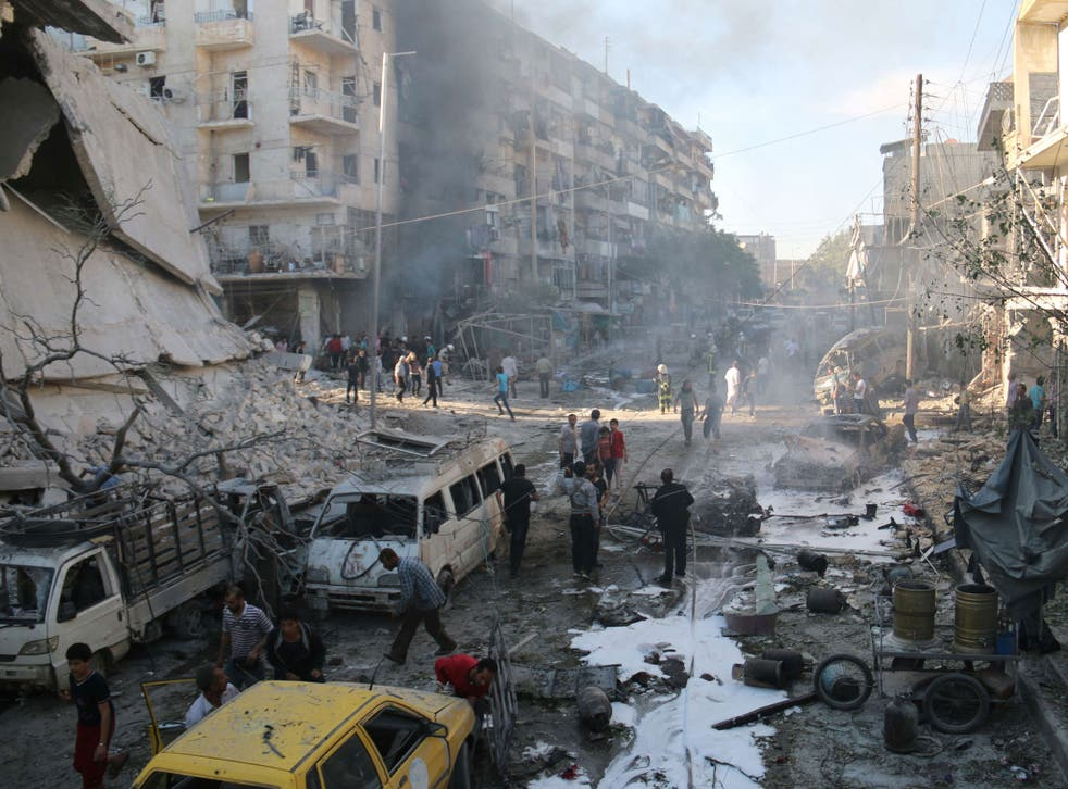 Syrians gather at the site of reported air strikes by government forces in the Halak neighbourhood in northeastern Aleppo