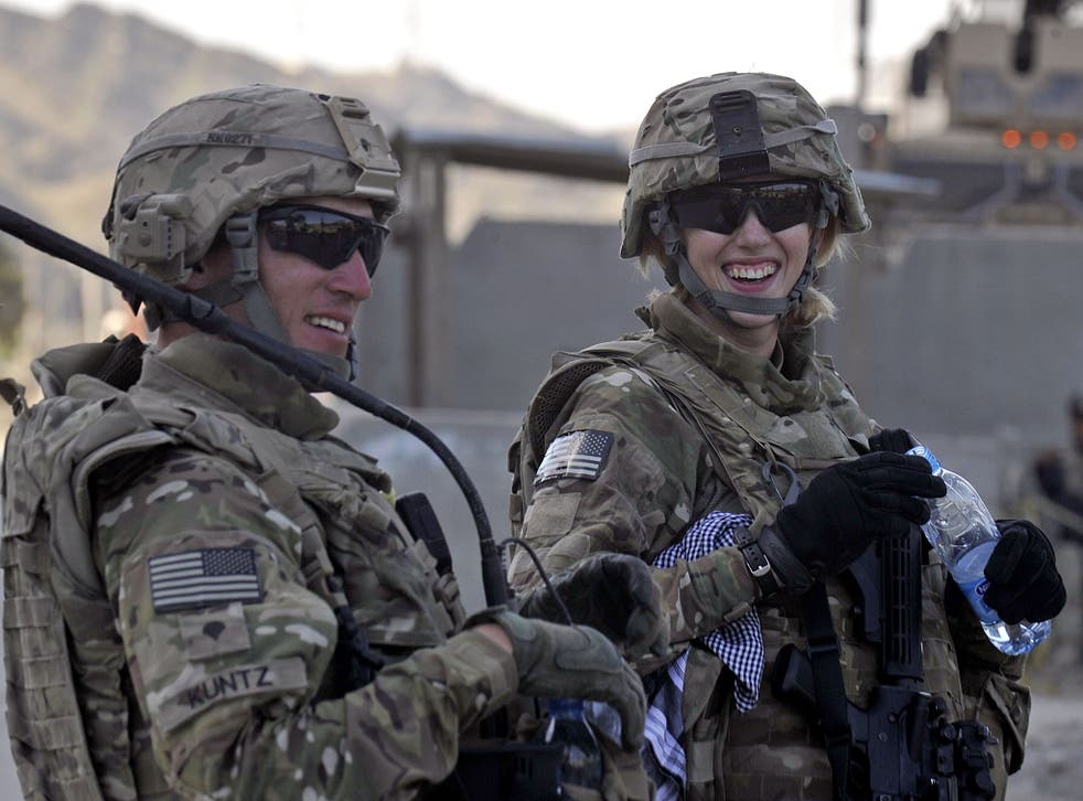 US army officers Kris Kuntz (L) and Hayley Barner talk in Afghanistan. Soon, UK female troops may be able to serve in 'close combat' positions.