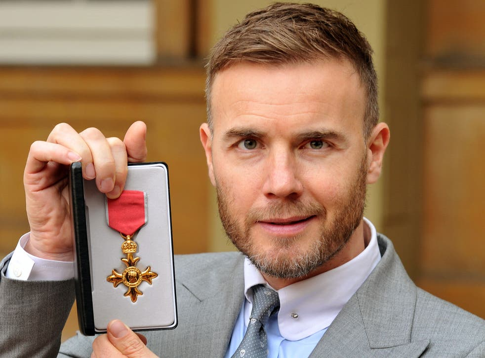 """Gary Barlow holding his OBE, as the Take That star faced calls to hand back his OBE over claims he invested in a tax avoidance scheme. PRESS ASSOCIATION Photo. Issue date: Monday May 12, 2014. Prime Minister David Cameron hit out at """"aggressive"""" tax avoid"""