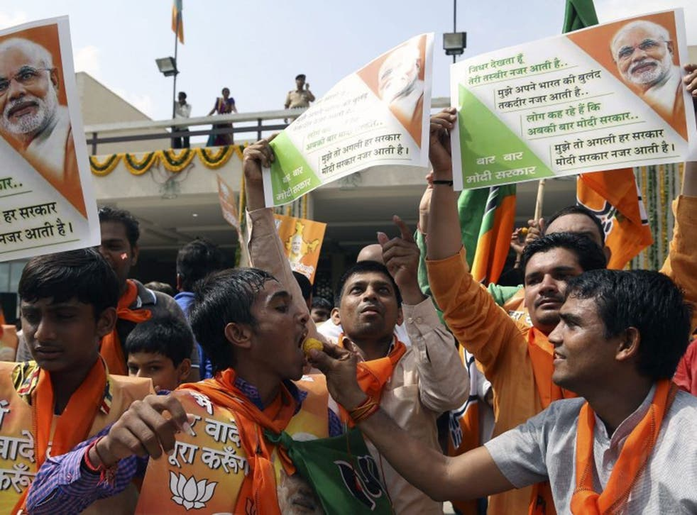 Supporters of Narendra Modi celebrate by dancing and distributing sweets at the BJP state headquarters in Gandhinagar, the capital of Gujarat