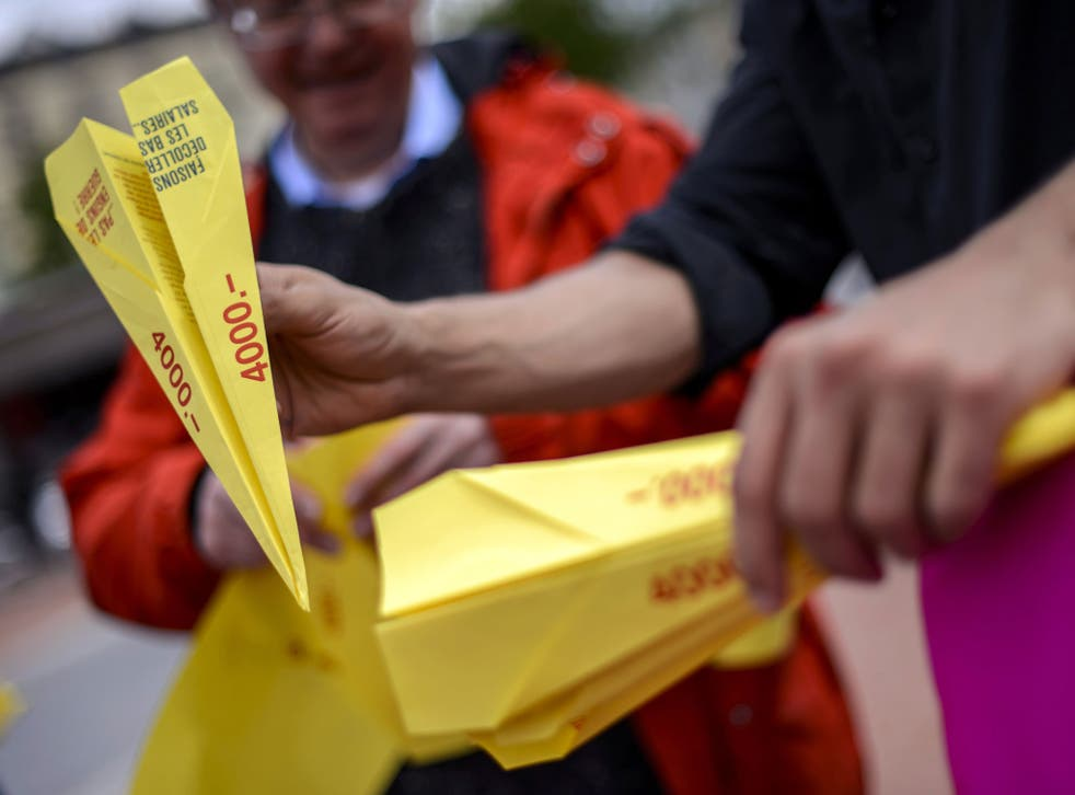 People hold paper planes during an action to support the minimum wage of 4000 Swiss Francs in Geneva.