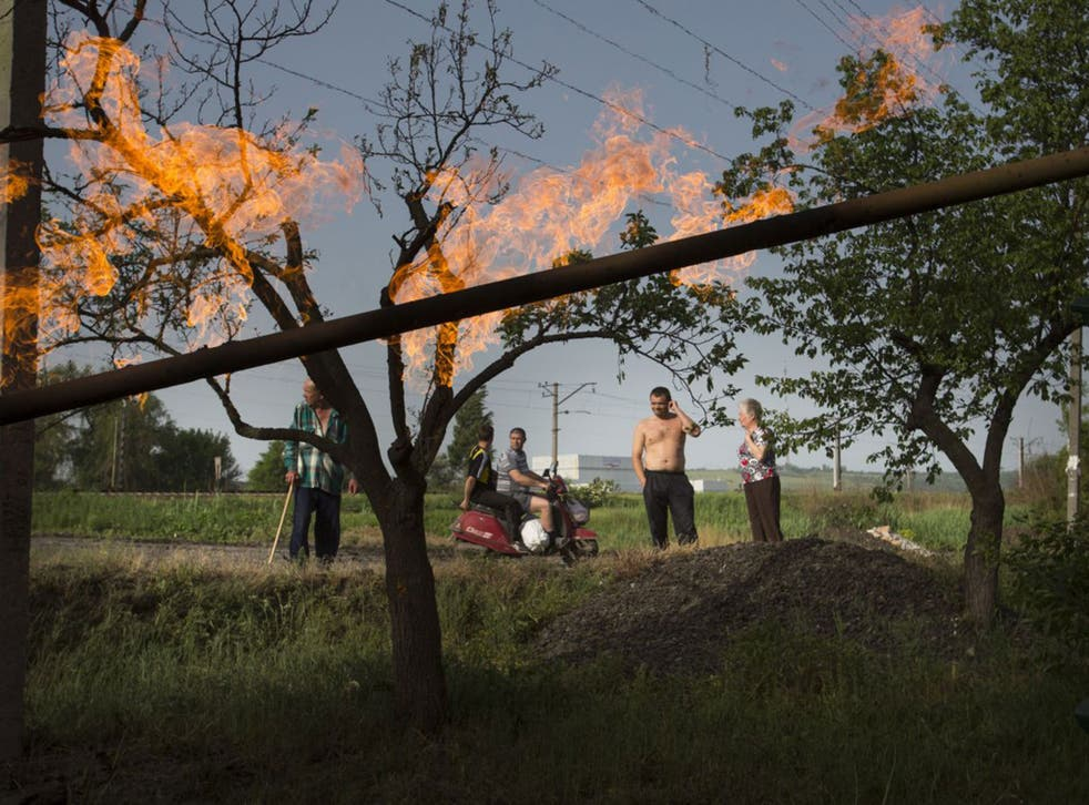 Residents watch flames from a gas pipe damaged by a mortar bomb during fighting in Slovyansk