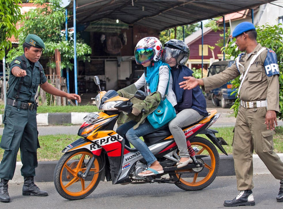 Sharia police stop a couple during an operation against women wearing tight jeans in Banda Aceh
