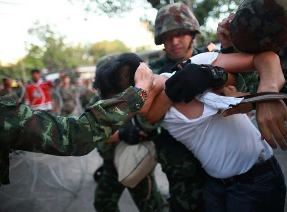 Soldiers grapple with a protester