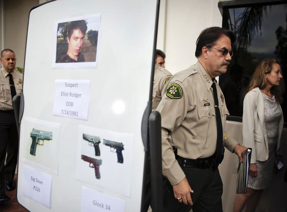 Santa Barbara County Sheriff Bill Brown, right, walks past a board showing the photos of suspected gunman Elliot Rodger and the weapons he used in Friday night's mass shooting