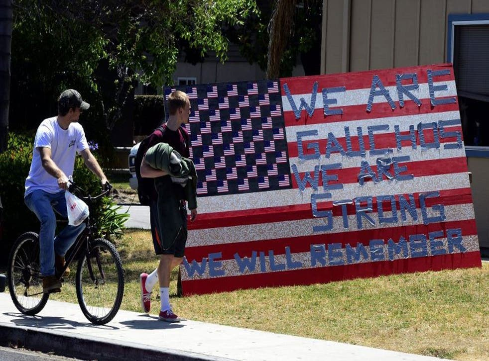 """Two students look at a sign that reads """"We are Gauchos, We are Strong, We will Remember"""" set up outside an apartment in the college town of Isla Vista, California"""