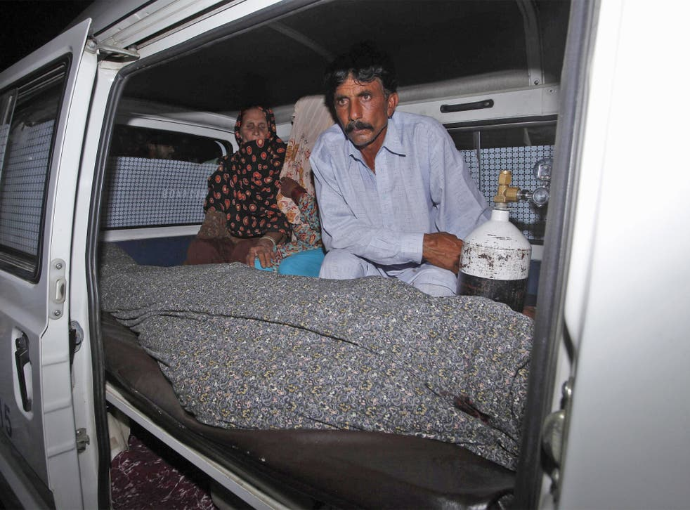 Mohammad Iqbal sits next to his wife Farzana's body in an ambulance in Lahore
