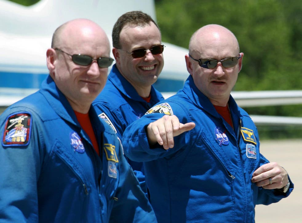 Shuttle Discovery commander Mark Kelly, right, gestures as he walks with his twin brother, astronaut Scott Kelly
