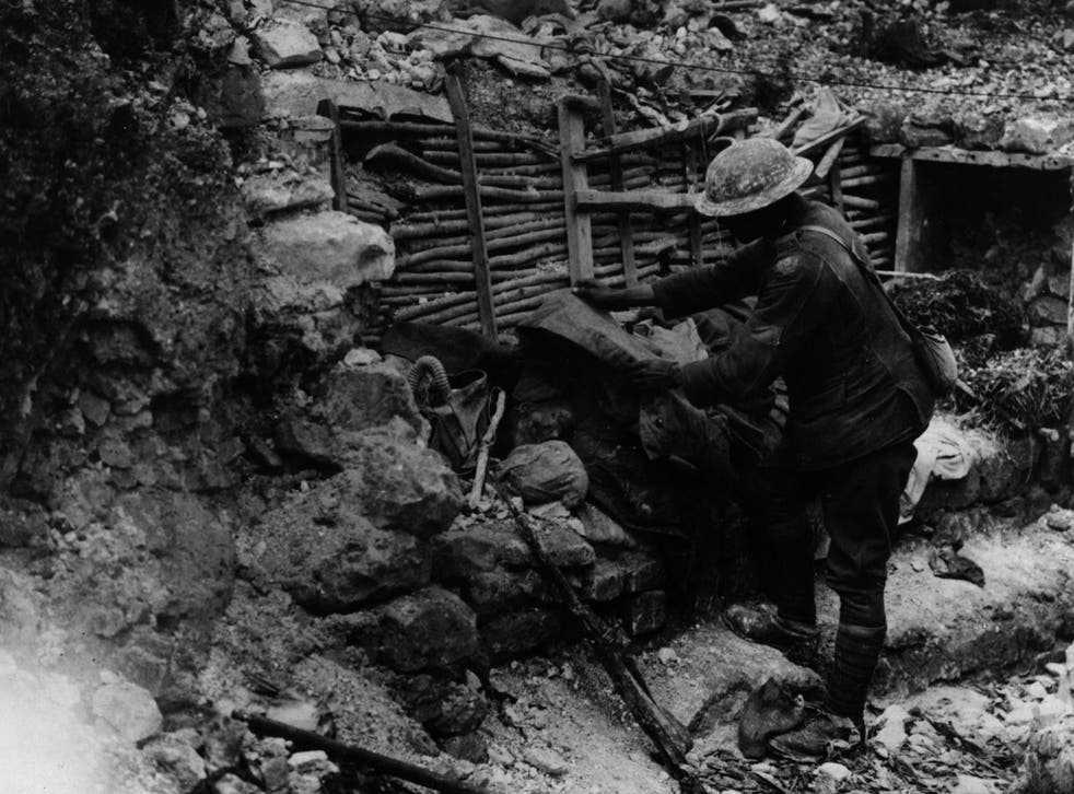 A British soldier covers a dead German on the firestep of a trench near the Somme
