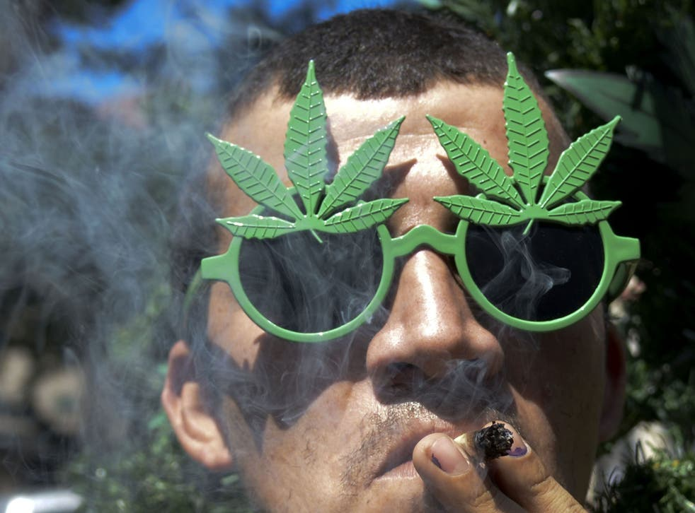 A man smokes marijuana during the World Day for the Legalization of Marijuana in Medellin, Antioquia department, Colombia on May 3, 2014.