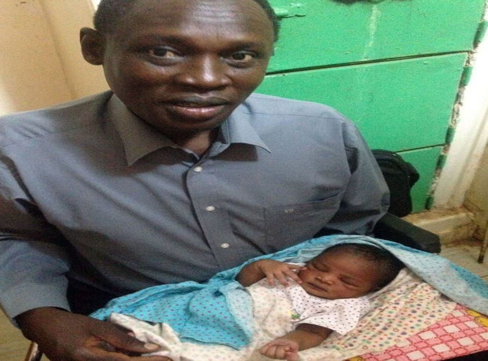 Daniel Wani, a US citizen originally from South Sudan, carrying his newborn daughter Maya at the womens prison in Khartoum's twin city of Omdurman