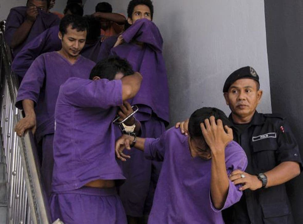 A picture made available 30 May 2014 shows Malaysian Police escorting gang-rape suspects to the courthouse in Kota Bharu, Kelantan, Malaysia, 29 May 2014.