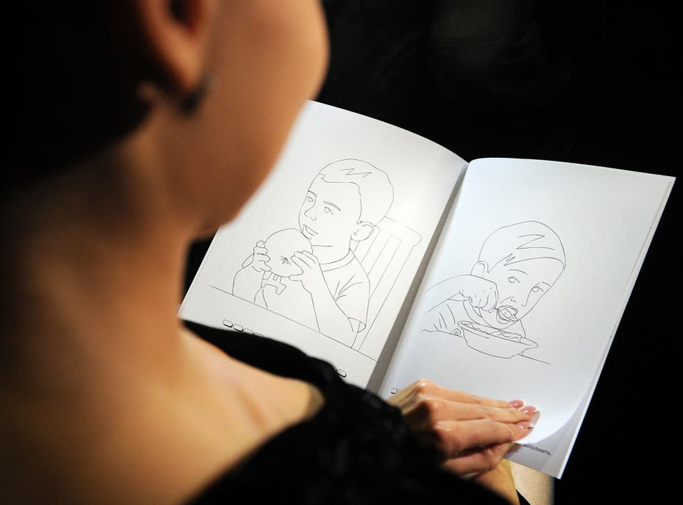 A woman holds a colouring book during a presentation in Moscow on October 6, 2011. A Moscow publishing house has released a children's colouring book in which two boys called Vova and Dima, closely resembling Prime Minister Vladimir Putin and President Dm