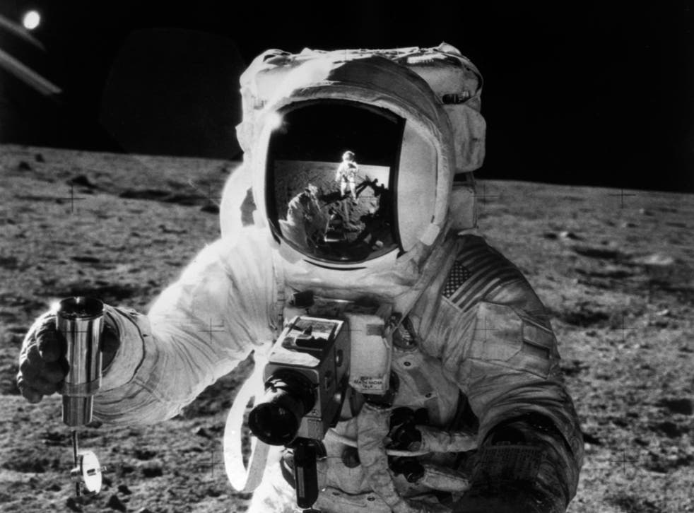 One of the astronauts of the Apollo 12 space mission conducting experiment on the moon's surface