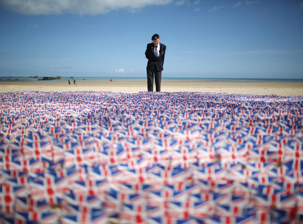 WW2 veteran Fred Holborn, from the Fleet Air Arm, looks at British Legion Union flags carrying thank you messages planted in the sand on Gold beach