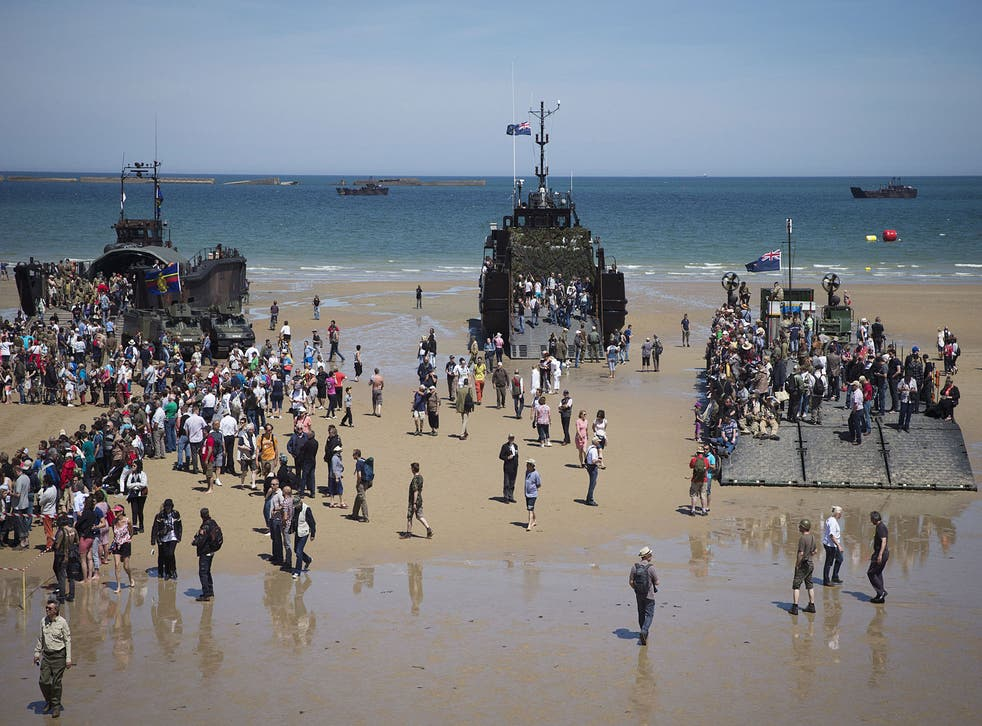 People visit Second World War landing crafts on the Arromanches beach, Normandy, on 6 June, 2014