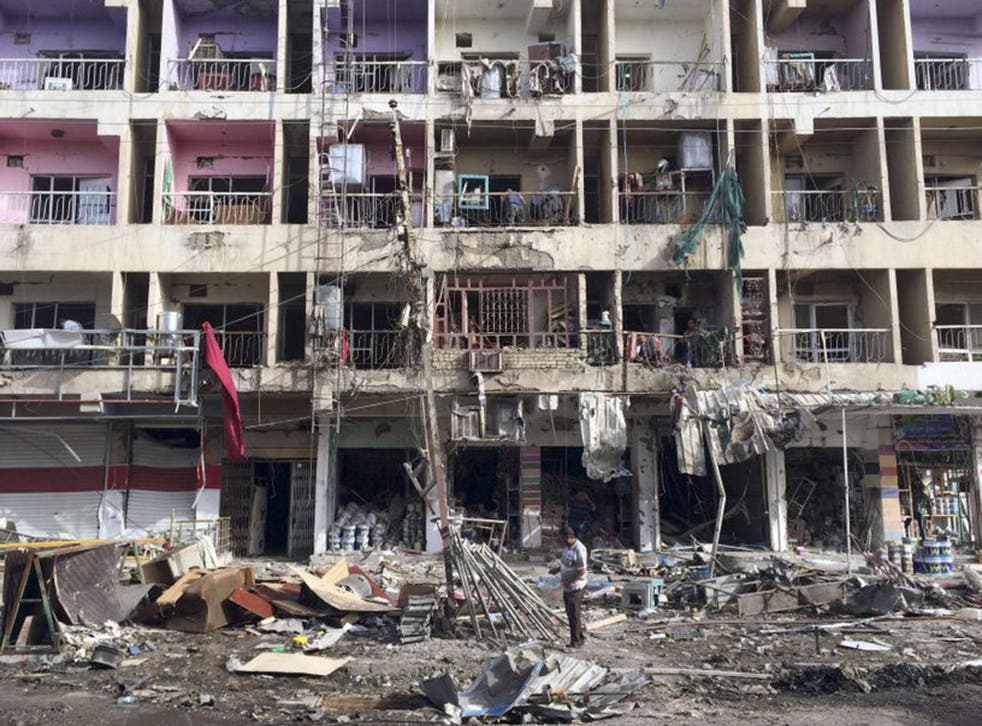 Iraqi civilians inspect the aftermath of a car bombing in south-east Baghdad in Iraq yesterday