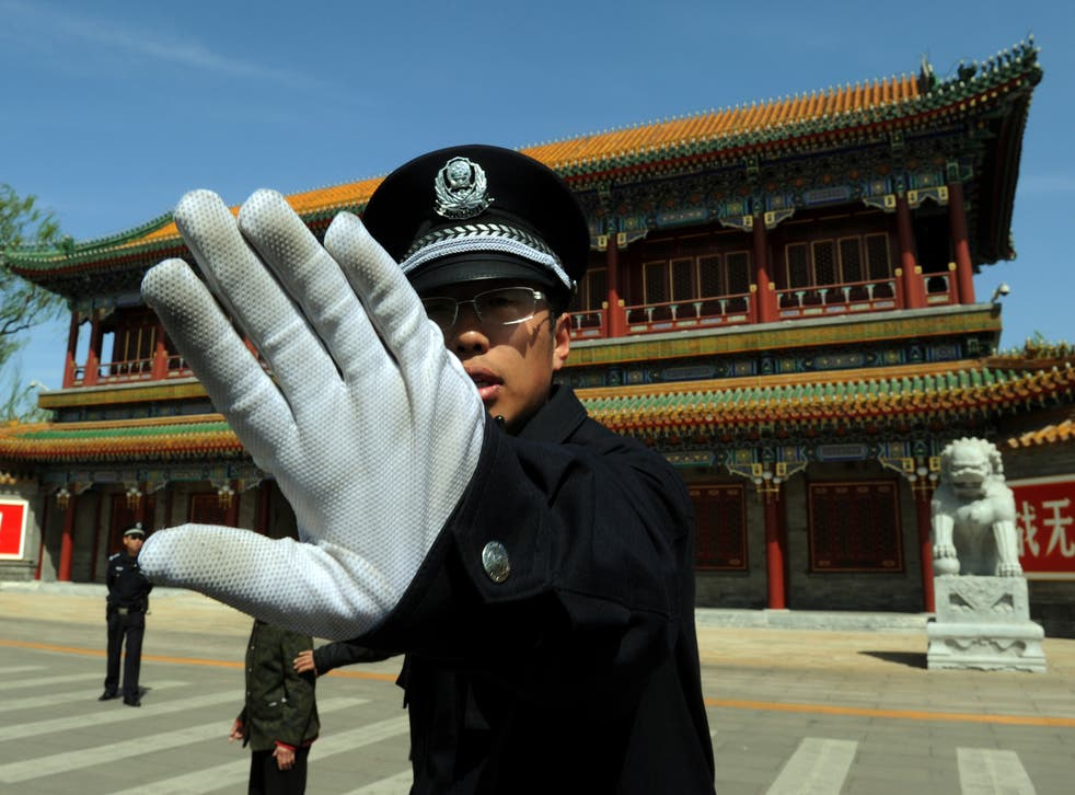 A Chinese policeman blocks photos being taken outside Zhongnanhai which serves as the central headquarters for the Communist Party of China