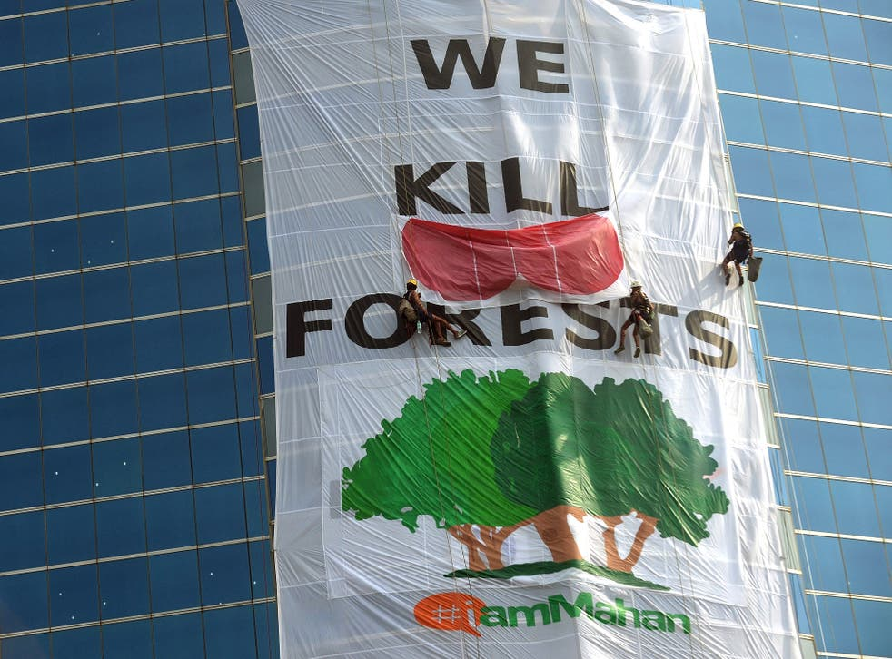 Greenpeace activists drape the headquarters of India's Essar Group with a giant banner during a protest in Mumbai earlier this year