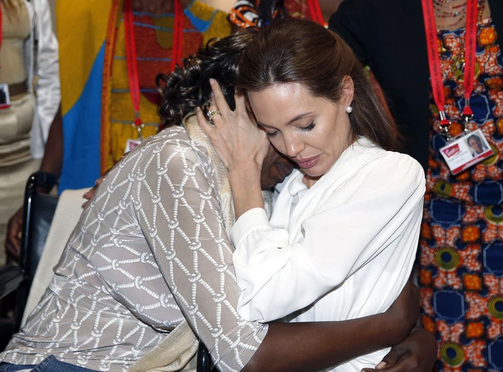 US actress and UN special envoy Angelina Jolie (R) embraces Neema Namadamu of the DRC during the second day of the Global Summit to End Sexual Violence in Conflict in London