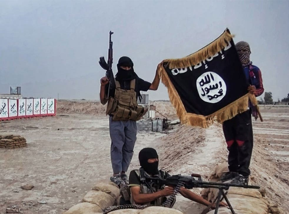 Isis rebels show their flag after seizing an army post