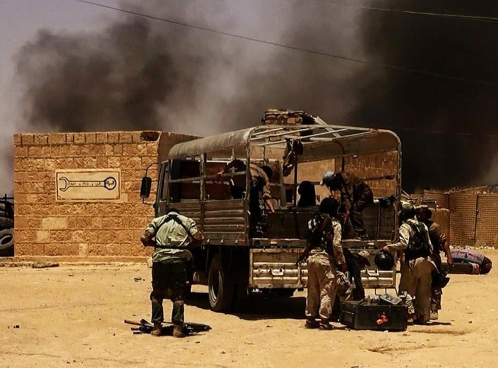 Isis militants take position at a checkpoint on the Syrian-Iraqi border