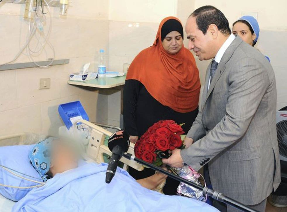 Egypt's President Abdel Fattah al-Sisi presents a bouquet of flowers to a woman who was sexually assaulted by a mob during Sunday's celebrations marking his inauguration, at a hospital in Cairo June 11, 2014