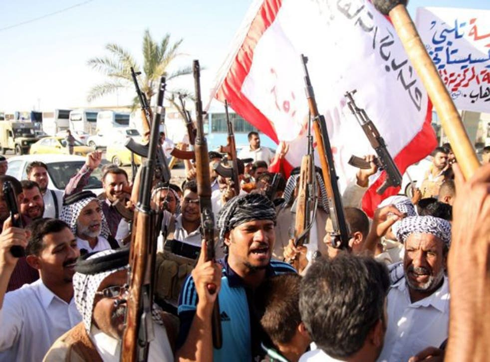 Iraqi volunteers carry their weapons and chant slogans in Karbala, southern Baghdad